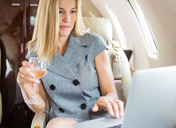 shutterstock 174642035%5b1%5dbusinesswoman holding wineglass while using laptop in airplane